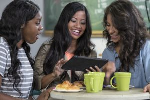 Three ethnically diverse young women sharing an ipad/tablet in a cafe